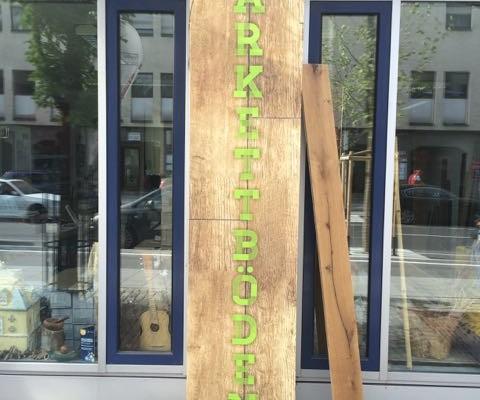 Werbebanner grün vertikal auf Holz